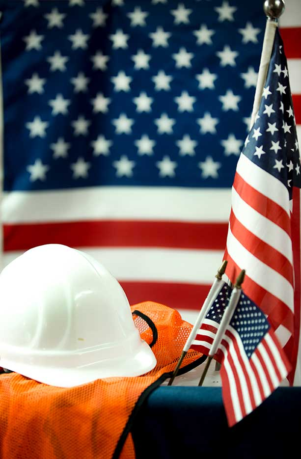 A hard hat and orange vest in front of an American flag