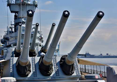 A battleship with large guns in a harbor