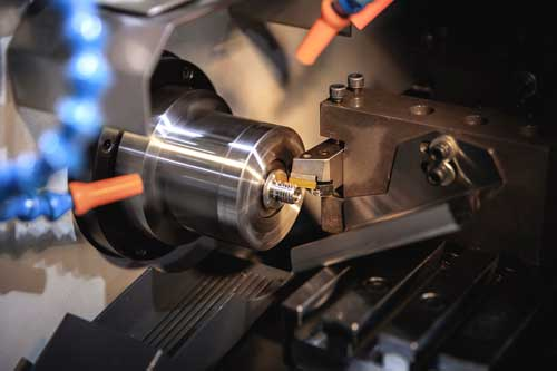 A CNC turning machine creating a part