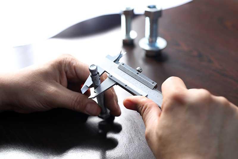 A person ensures part quality using a caliper