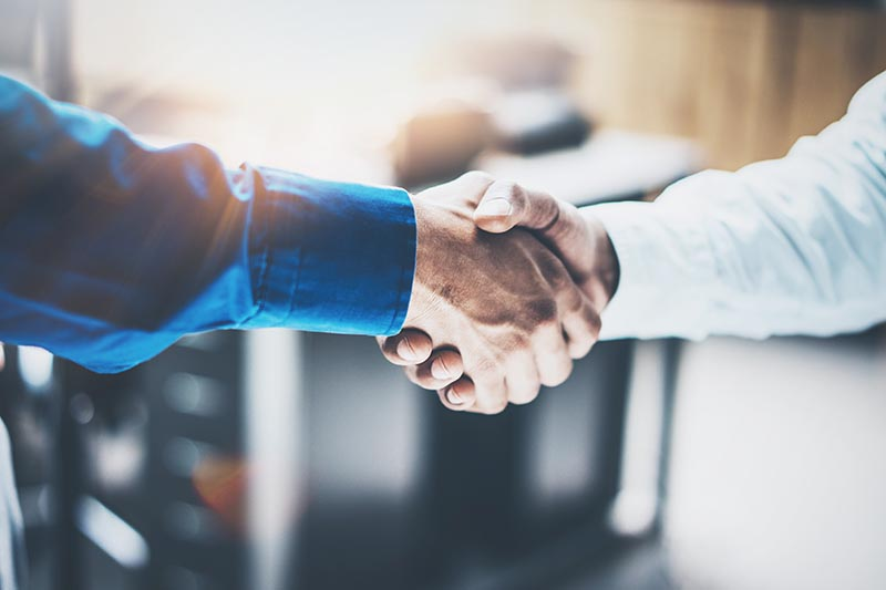 Close up view of two men shaking hands